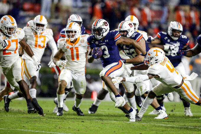 Auburn running back D.J. Williams (3) carries the ball as he gets past the arms of Tennessee defensive back Warren Burrell (4) during the first half of an NCAA college football game on Saturday, Nov. 21, 2020, in Auburn, Ala. (AP Photo/Butch Dill)