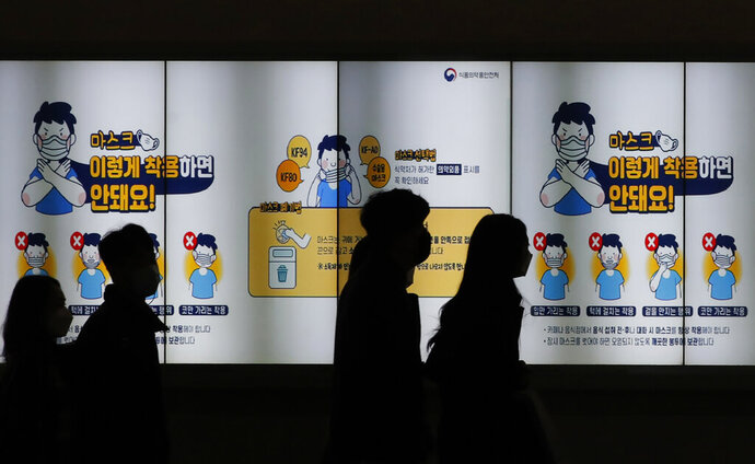 People wearing face masks walk past a screen showing the precautions against the coronavirus in Seoul, South Korea, Friday, Nov. 20, 2020. The screen reads: