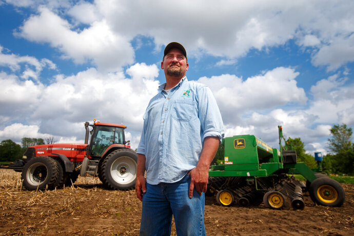 In this May 22, 2019, photo, farmer Tim Bardole pauses for a photo as he plants a field near Perry, Iowa. Donald Trump won the presidency by winning rural America, in part by pledging to use his business savvy and tough negotiating skills to take on China and put an end to trade practices that have hurt farmers for years. While the prolonged fight has been devastating to an already-struggling agriculture industry, there's little indication Trump is paying a political price. (Zach Boyden-Holmes/The Des Moines Register via AP)