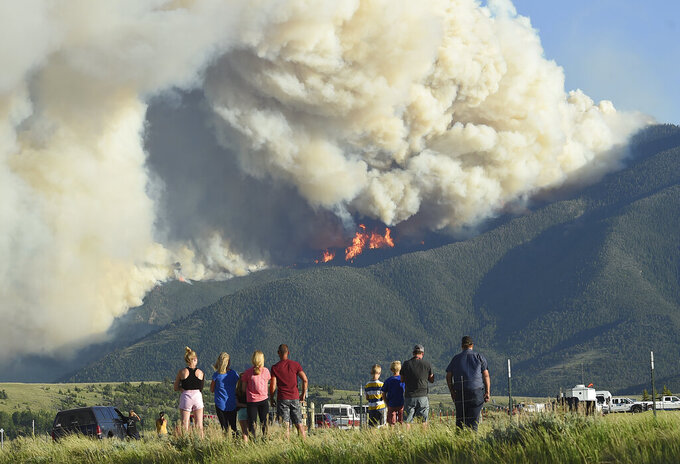 Residents watch as flames from the Robertson Draw fire burn above Red Lodge, Mont., Tuesday evening, June 15, 2021. Wildfires burning in Montana exploded in size over the past 24 hours and triggered evacuations of people from rural areas as scorching heat and heavy winds stoked the blazes. (Larry Mayer/The Billings Gazette via AP)