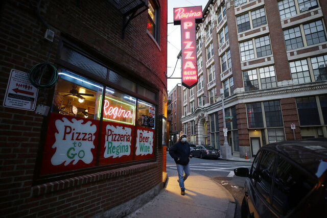 A patron walks near an entrance to a pizza restaurant, in Boston's North End neighborhood, Monday, March 16, 2020. Mass. Gov. Charlie Baker issued an emergency order Sunday that includes a ban on on-premises consumption of food or drink at bars and restaurants, beginning on March 17 and lasting until April 6 in response to the coronavirus. For most people, the new coronavirus causes only mild or moderate symptoms, such as fever and cough. For some, especially older adults and people with existing health problems, it can cause more severe illness, including pneumonia. The vast majority of people recover from the new virus. (AP Photo/Steven Senne)