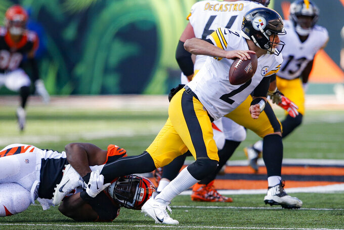 Pittsburgh Steelers quarterback Mason Rudolph (2) looks to pass under pressure from Cincinnati Bengals defensive end Carl Lawson, left, during the first half an NFL football game, Sunday, Nov. 24, 2019, in Cincinnati. (AP Photo/Gary Landers)