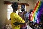 In this photo taken Thursday, June 11, 2020, Ugandan gay refugee Martin Okello, right, greets a friend in the house he shares with other Ugandan LGBT refugees in Nairobi, Kenya. Although Kenya is seen as a haven for LGBT refugees, Okello says he still faces discrimination and violence there, and he keeps a low profile. He was attacked and beaten last month by assailants. (AP Photo/Brian Inganga)