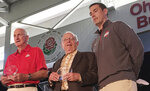 CORRECTS TO EARLE, NOT EARL AS ORIGINALLY SENT - FILE - In this April 15, 2016, file photo, former Ohio State football coach Earle Bruce is flanked by former Ohio State football coaches John Cooper, left, and Luke Fickell, at a high school coaches clinic in Columbus, Ohio. Former Ohio State football coach Earle Bruce has died at his home in central Ohio. The College Football Hall of Fame member was 87. His four daughters released a statement Friday, April 20, 2018, on the loss of