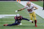 San Francisco 49ers tight end George Kittle (85) eludes New England Patriots defensive back J.C. Jackson (27) after catching a pass in the first half of an NFL football game, Sunday, Oct. 25, 2020, in Foxborough, Mass. (AP Photo/Steven Senne)