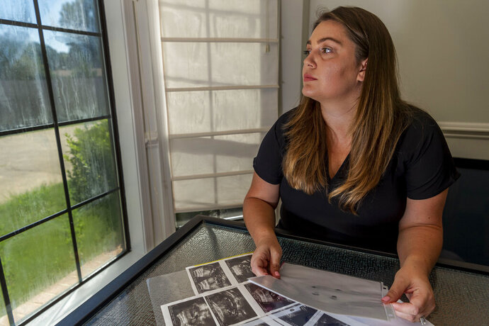 ADVANCE FOR RELEASE SUNDAY, SEPT. 8, 2019, AND THEREAFTER - In this Aug. 29, 2019, photo, Hevan Lunsford poses for a photo with her son's ultrasounds and footprints and handprints of her son, in Prattville, Ala. Lunsford found out when she was five months pregnant that the baby she would later name Sebastian was severely underdeveloped and had only half of a heart. Lunsford said she felt the only way to guarantee her son would not suffer would be to end the pregnancy and was told she would need to travel to Georgia for the procedure. Lunsford is one of thousands of women across the U.S. in recent years who have crossed state lines for an abortion. (AP Photo/Vasha Hunt)