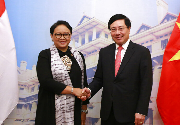 Indonesian Foreign Minister Retno Marsudi, left, shakes hands with her Vietnamese counterpart Pham Binh Minh before heading for talks in Hanoi, Vietnam, Tuesday, April 17, 2018. The two countries pledge to work together to resolve the fishing violations in the South China Sea as the they seek to boost their bilateral trade. (AP Photo/Tran Van Minh)