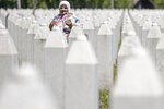 A woman prays at the memorial cemetery in Potocari, near Srebrenica, Bosnia, Friday, July 10, 2020. Nine newly found and identified men and boys will be laid to rest when Bosnians commemorate on Saturday 25 years since more than 8,000 Bosnian Muslims perished in 10 days of slaughter, after Srebrenica was overrun by Bosnian Serb forces during the closing months of the country's 1992-95 fratricidal war, in Europe's worst post-WWII massacre. (AP Photo/Kemal Softic)