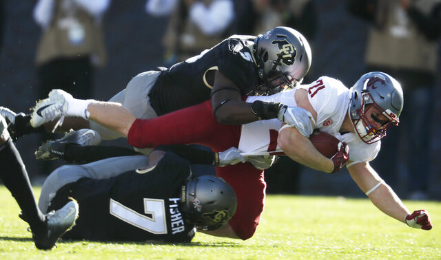 FILE - In this Nov. 10, 2018, file photo, Washington State running back Max Borghi, center, is tackled after a short gain by Colorado linebacker Davion Taylor, top, and defensive back Nick Fisher in the first half of an NCAA college football game in Boulder, Colo. Taylor took an unusual path to the cusp of the NFL draft. He did not play in high school because of his religion and spent two years at a community college before spending two seasons at the University of Colorado. (AP Photo/David Zalubowski, File)