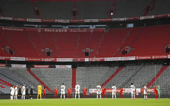 Players pay a minute of silence for the victims of the coronavirus prior to the German Bundesliga soccer match between Bayern Munich and Eintracht Frankfurt in Munich, Germany, Saturday, May 23, 2020. (Andreas Gebert/pool via AP)