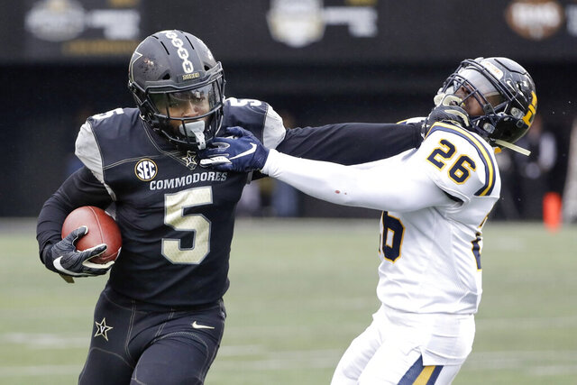 Vanderbilt running back Ke'Shawn Vaughn (5) tries to get past ETSU defensive back Artevius Smith (26) in the first half of an NCAA college football game Saturday, Nov. 23, 2019, in Nashville, Tenn. (AP Photo/Mark Humphrey)