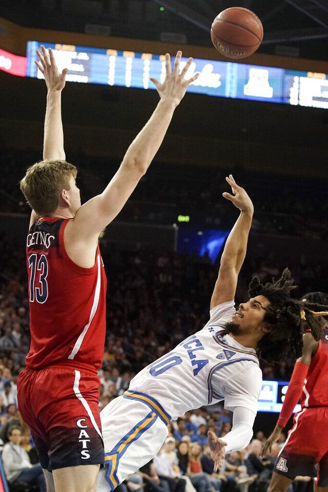 UCLA guard Tyger Campbell, right, shoots over Arizona forward Stone Gettings during the second half of an NCAA college basketball game in Los Angeles, Saturday, Feb. 29, 2020. UCLA won 69-64. (AP Photo/Chris Carlson)