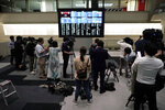 Journalists film an electronic stock board showing reopening of Japan's Nikkei 225 index at Tokyo Stock Exchange in Tokyo Friday, Oct. 2, 2020. Tokyo's market resumed trading Friday after a full-day outage due to a malfunction in its computer systems. (AP Photo/Eugene Hoshiko)