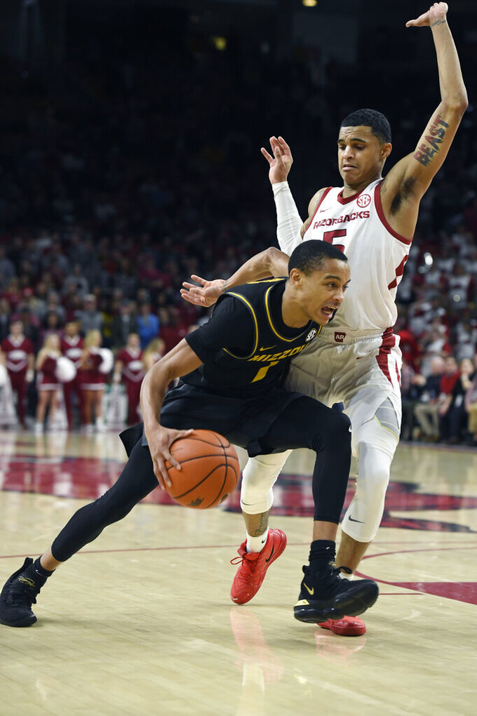 Missouri guard Xavier Pinson (1) tries to drive past Arkansas defender Jalen Harris (5) during the second half of an NCAA college basketball game, Wednesday, Jan. 23, 2019, in Fayetteville, Ark. (AP Photo/Michael Woods)