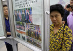 In this Wednesday, June 13, 2018, photo, people read a newspaper dominated with news on the summit between U.S. President Donald Trump and North Korean leader Kim Jong Un at a subway station in Pyongyang, North Korea. North Koreans are getting a new look at U.S. President Donald Trump now that his summit with leader Kim Jong Un is safely over and it's a far cry from the