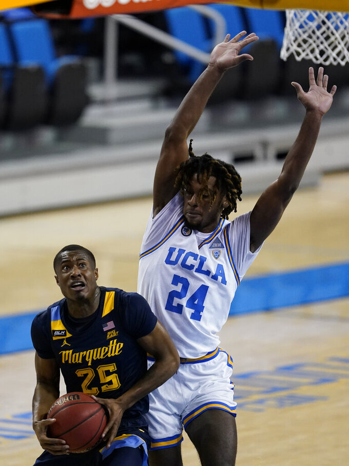 UCLA forward Jalen Hill, right, defends against Marquette guard Koby McEwen during the first half of an NCAA college basketball game Friday, Dec. 11, 2020, in Los Angeles. (AP Photo/Ashley Landis)