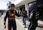 Mercedes driver Lewis Hamilton of Britain, right, after setting a pole position fist bumps with third placed Red Bull driver Max Verstappen of the Netherlands after the qualifying session for the Hungarian Formula One Grand Prix, at the Hungaroring racetrack in Mogyorod, Hungary, Saturday, July 31, 2021. The Hungarian Formula One Grand Prix will be held on Sunday. (David W Cerny/Pool via AP)