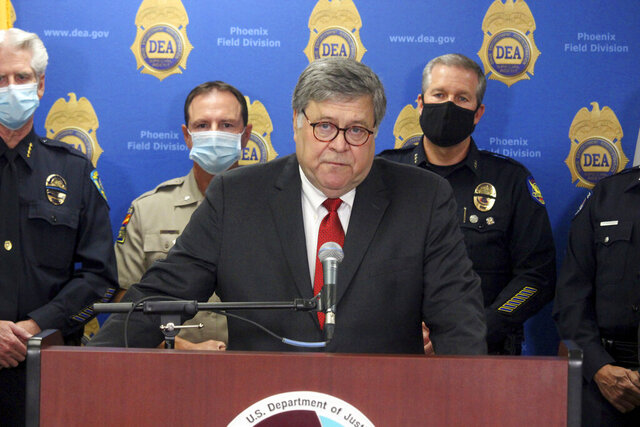 U.S. Attorney General William Barr speaks at a news conference, Thursday, Sept. 10, 2020, in Phoenix, where he announced results of a crackdown on international drug trafficking. Barr spent much of his time attacking mail-in voting, defending a Justice Department decision to take over defense of President Trump in a defamation case and discussing the civil unrest triggered by the killing of George Floyd by Minneapolis police in May. (AP Photo/Bob Christie)