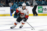 Calgary Flames left wing Johnny Gaudreau (13) skates in front of San Jose Sharks center Patrick Marleau during the first period of an NHL hockey game in San Jose, Calif., Sunday, Oct. 13, 2019. (AP Photo/Jeff Chiu)