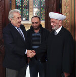 In this photo released by the Lebanese Government, Lebanon's Grand Mufti Sheikh Abdul Latif Derian, right, shakes hand with Samir Khatib, the head of a major contracting and construction and once considered a favorite candidate for the post of Prime Minister, in Beirut, Lebanon, Sunday, Dec. 8, 2019. (Dalati Nohra via AP)