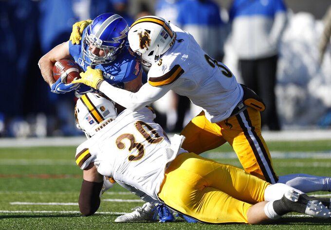 Air Force running back Kadin Remsberg, back left, is pulled down by Wyoming linebacker Logan Wilson, front left, and safety Alijah Halliburton after a short gain in the second half of an NCAA college football game Saturday, Nov. 30, 2019, at Air Force Academy, Colo. Air Force won 20-6. (AP Photo/David Zalubowski)
