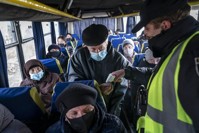A policeman checks temperatures of passengers riding a bus at the checkpoint near Ivano-Frankivsk, Ukraine, Thursday, Feb. 25, 2021. Ukraine has recorded a 50% increase in the number of daily new coronavirus infections, as the country takes the first steps in its vaccination campaign. Health Minister Maxim Stepanov said Thursday that 8,417 new infections were found over the past day, up from 5,424 a day earlier. (AP Photo/Evgeniy Maloletka)