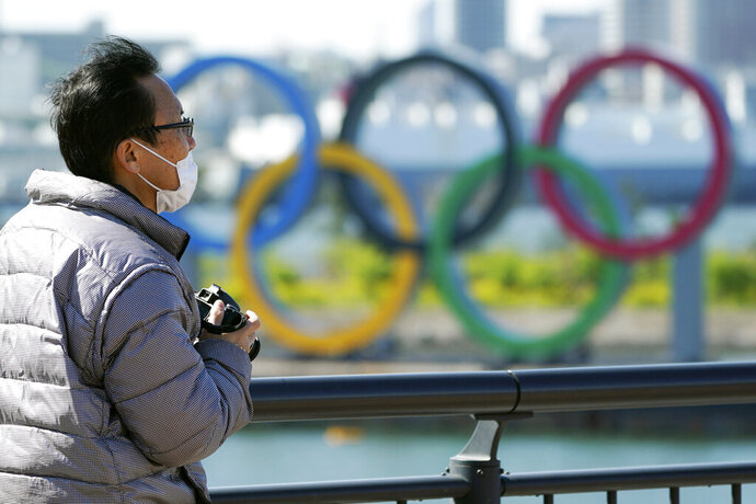 A visitor wearing a face mask stands near the Olympic rings at Tokyo's Odaiba district Tuesday, March 24, 2020. The Tokyo Olympics are probably going to happen, but almost surely in 2021 rather than in four months as planned. (AP Photo/Eugene Hoshiko)