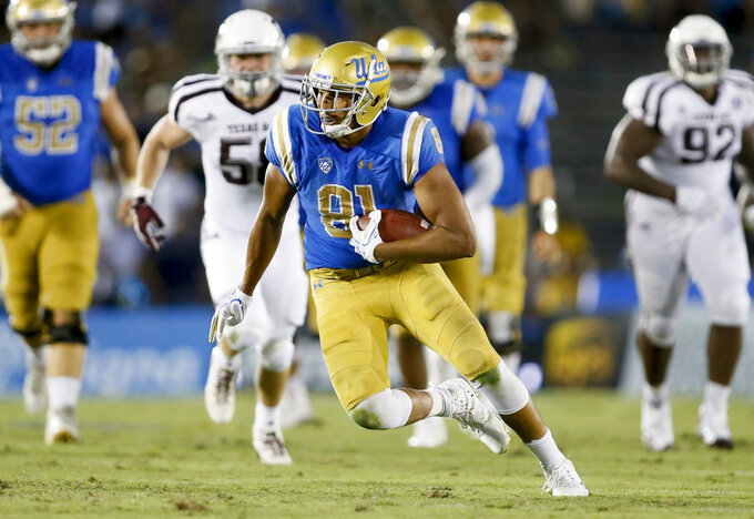 FILE - In this Sept. 3, 2017, file photo, UCLA tight end Caleb Wilson runs with the ball against Texas A&M during an NCAA college football game in Pasadena, Calif. Wilson had 38 caches for 490 yards in only five games last season before a foot injury shut him down for the rest of the year. (AP Photo/Danny Moloshok, File)