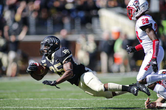 Wake Forest running back Kenneth Walker, left, dives ahead of North Carolina State cornerback Kishawn Miller in the first half of an NCAA college football game in Winston-Salem, N.C., Saturday, Nov. 2, 2019. (AP Photo/Nell Redmond)