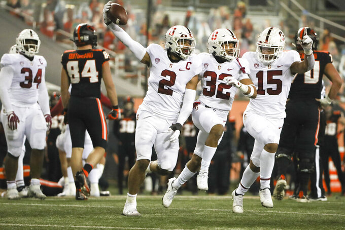 Stanford's Curtis Robinson (2), Jonathan McGill (32) and Stephen Herron (15) celebrate Robinson's recovery of an Oregon State fumble during the last minute of the second half in an NCAA college football game in Corvallis, Ore., Saturday, Dec. 12, 2020. Stanford won 27-24. (AP Photo/Amanda Loman)