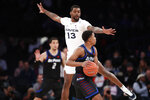 Xavier forward Naji Marshall (13) defends against DePaul guard Charlie Moore (11) during the first half of an NCAA college basketball game in the first round of the Big East men's tournament Wednesday, March 11, 2020, in New York. (AP Photo/Kathy Willens)