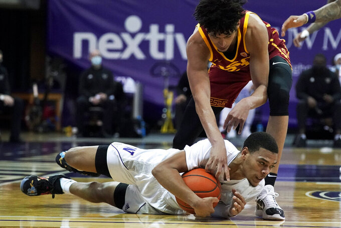 Washington guard Quade Green, bottom, holds on to the ball as Southern California forward Max Agbonkpolo, top, reaches for it during the first half of an NCAA college basketball game Thursday, Feb. 11, 2021, in Seattle. (AP Photo/Ted S. Warren)