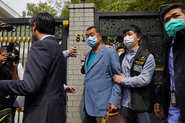 Hong Kong media tycoon Jimmy Lai, center, who founded local newspaper Apple Daily, is arrested by police officers at his home in Hong Kong, Saturday, April 18, 2020. Hong Kong police arrested at least 14 pro-democracy lawmakers and activists on Saturday on charges of joining unlawful protests last year calling for reforms. (AP Photo/Vincent Yu)