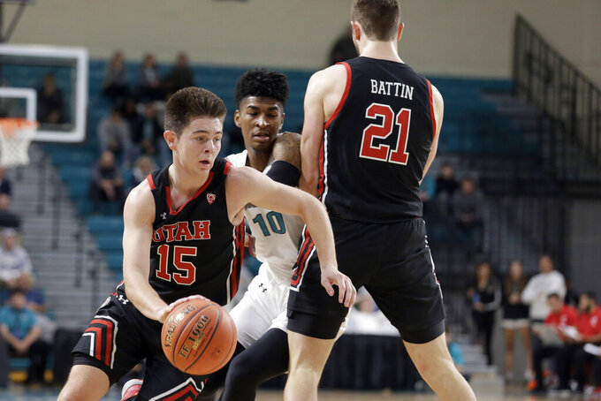 Utah guard Rylan Jones (15) gets a screen from forward Riley Battin (21) against Coastal Carolina guard Tyrell Gumbs-Frater (10) during the first half of an NCAA college basketball game at the Myrtle Beach Invitational in Conway, S.C., Thursday, Nov. 21, 2019. (AP Photo/Gerry Broome)
