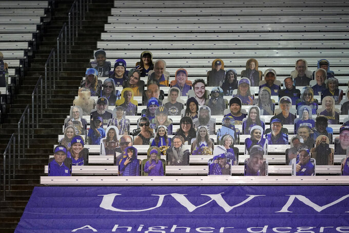 Photos of fans sit in otherwise empty seats at Husky Stadium before an NCAA college football game between Washington and Oregon State, Saturday, Nov. 14, 2020, in Seattle. Due to the COVID-19 pandemic, no fans were in attendance at the game. (AP Photo/Ted S. Warren)
