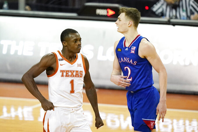 Texas guard Andrew Jones (1) celebrates in front of Kansas guard Christian Braun (2) after making a basket during the second half of an NCAA college basketball game, Tuesday, Feb. 23, 2021, in Austin, Texas. (AP Photo/Eric Gay)