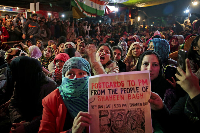 In this Saturday, Jan. 18, 2020 photo, women protesters shout slogans at the protest site at Shaheen Bagh area in New Delhi, India. Muslim women are transcending the confines of their homes to lay claim to the streets of this nondescript Muslim neighborhood in the Indian capital and slowly transforming it into a nerve center of resistance against a new citizenship law that has unleashed protests across the country. The women, sitting in the middle of a major highway, have taken turns maintaining an around the clock sit-in for more than a month. They sing songs of protest and chant anti-government slogans, some cradling babies, others laying down rugs to make space for more people to sit. (AP Photo/Altaf Qadri)