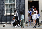 School children approach Downing Street chief mouser Larry the cat, as they leave after a scheduled meeting with Britain's Prime Minister Boris Johnson at 10 Downing Street in London, Friday, Aug. 30, 2019.(AP Photo/Frank Augstein)