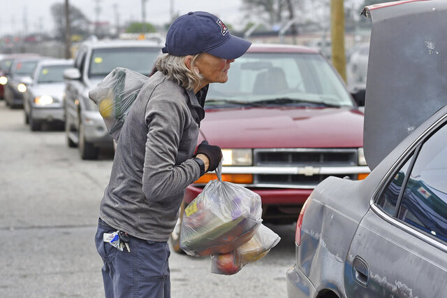A volunteer loads groceries at a drive-thru and pick up location at Harvest Hope Food Bank Wednesday, March 18, 2020, in Greenville, S.C. Harvest Hope helps low income families and senior citizens. (AP Photo/Richard Shiro)