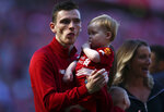 Liverpool's Andrew Robertson holds a child at the end of the English Premier League soccer match between Liverpool and Wolverhampton Wanderers at the Anfield stadium in Liverpool, England, Sunday, May 12, 2019. Despite a 2-0 win over Wolverhampton Wanderers, Liverpool missed out on becoming English champion for the first time since 1990 because title rival Manchester City beat Brighton 4-1. (AP Photo/Dave Thompson)