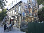 Cyclists chat beside a historical fresco in Old Quebec, Aug. 31, 2017. Nearby, the Promenade Samuel de Champlain path takes cyclists along the St. Lawrence River, past outdoor works of art and the lively waterfront, connecting them with a path across the river via the ferry or bridge. (AP Photo/Cal Woodward)