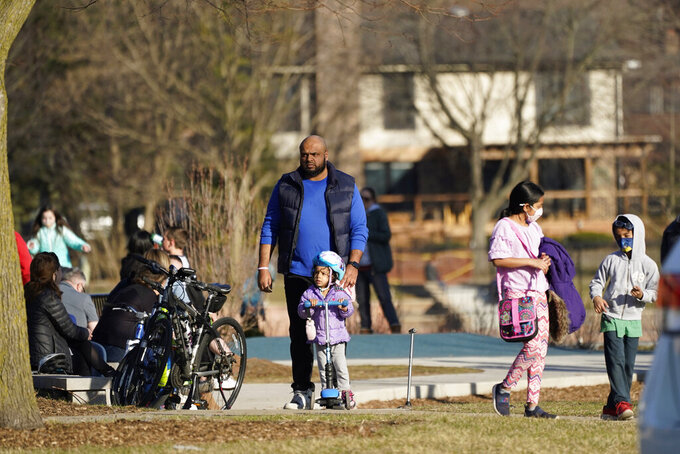 People enjoy the mild weather at the Burning Bush Trails park in Mount Prospect, Ill., Saturday, March 13, 2021. Illinois Gov. J.B. Pritzker announced on Friday that all Illinois adults could be eligible for a coronavirus vaccine before May. (AP Photo/Nam Y. Huh)