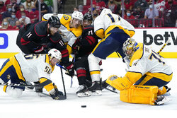 Carolina Hurricanes center Jordan Staal (11) and right wing Jesper Fast (71) struggle for the puck against Nashville Predators goaltender Juuse Saros (74) while Predators left wing Erik Haula (56), left wing Tanner Jeannot and defenseman Ben Harpur (17) defend during the second period in Game 5 of an NHL hockey Stanley Cup first-round playoff series in Raleigh, N.C., Tuesday, May 25, 2021. (AP Photo/Gerry Broome)