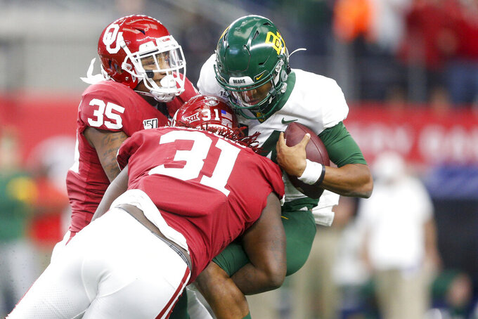 Oklahoma linebacker Nik Bonitto (35) and defensive tackle Jalen Redmond (31) sack Baylor Bears quarterback Jacob Zeno (14) in overtime in an NCAA college football game for the Big 12 Conference championship, Saturday, Dec. 7, 2019, in Arlington, Texas. (Ian Maule/Tulsa World via AP)