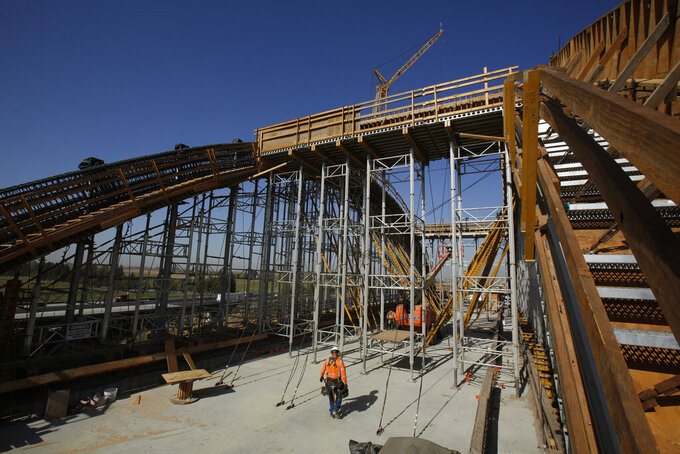 """FILE - This Oct. 9, 2019, file photo, shows the high speed rail viaduct under construction over the San Joaquin River near Fresno, Calif. California Gov. Gavin Newsom on Friday, May 14, 2021, proposed spending $11 billion on transportation improvements, half of it for a troubled bullet train intended to eventually link California's major metropolitan areas and for projects supporting the 2028 Summer Olympics in Los Angeles. High-Speed Rail Authority spokeswoman Melissa Figueroa said Newsom """"expressed the optimism we all share"""" that the federal government will now provide $929 million withdrawn by Trump's administration. (AP Photo/Rich Pedroncelli, File)"""