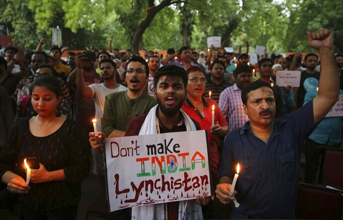 FILE- In this June 26, 2019 file photo, Indian protesters shout slogans as they hold placards and candles during a protest condemning mob lynching of Muslim youth Tabrez Ansari in Jharkhand state, in New Delhi, India. Dozens of Indian celebrities have asked Prime Minister Narendra Modi to intervene and stop rising incidents of attacks on minorities, misuse of religion by Hindu hard-liners and intolerance against dissent in the country. (AP Photo/Altaf Qadri, File)