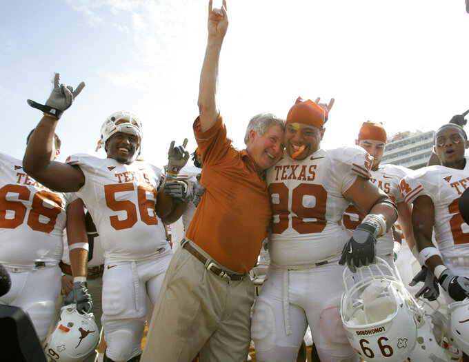 FILE - In this Oct. 11, 2008, file photo, Texas coach Mack Brown celebrates with Texas defensive tackle Roy Miller (99) and others after beating No. 1 Oklahoma 45-35 in an NCAA college football game, in Dallas. The annual Texas-Oklahoma rivalry game in Dallas decided the Big 12 more often than not. Both teams were nationally ranked in nine of the ten meetings. Oklahoma won the first five from 2000-04 but Texas bounced back by winning four of the last five. (AP Photo/Tony Gutierrez, File)