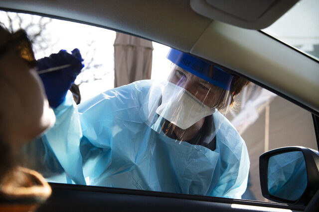 A nurse with Cooper administers a test for the new coronavirus at a drive-thru site, Wednesday, April 1, 2020, in Cherry Hill, N.J. (Joe Lamberti/Camden Courier-Post via AP)