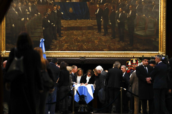 In this Tuesday, July 9, 2019 photo, relatives of former Argentine President Fernando De la Rua stand beside his coffin during his wake inside Congress in Buenos Aires, Argentina. De la Rua, who attracted voters with his image as an honest statesman and later left as the country plunged into its worst economic crisis, died Tuesday at 81. (AP Photo/Natacha Pisarenko)