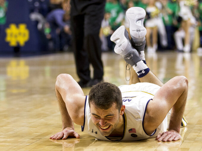 Notre Dame's John Mooney grimaces in pain after an injury during the second half of an NCAA college basketball game against Boston College Saturday, Jan. 12, 2019, in South Bend, Ind. Notre Dame won 69-66. (AP Photo/Robert Franklin)
